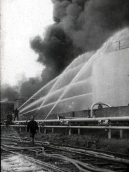 Firefighters spraying water over a large gas tank