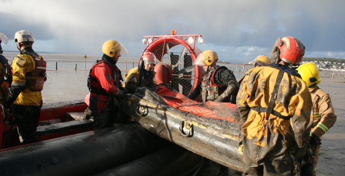 Firefighters carry an inflatable stretcher from a hovercraft