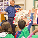 Firefighter educating a class of school children about fire safety