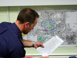 Staff member studying a map and referring to a list
