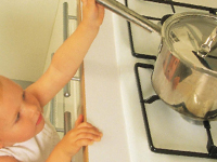 Child reaching for a pan on a stove