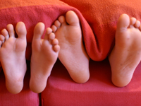 Two pairs of feet sticking out the end of a bed